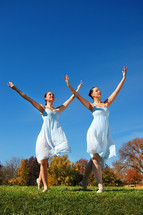 Two women dancers outdoors dancing on the grass, autumn trees in the background