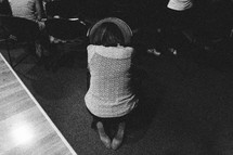 woman kneeling in prayer over a chair