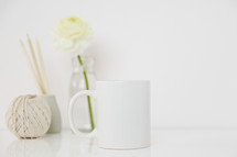 white flower in a clear vase, twine, coffee mug