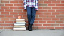 a kid standing next to a stack of books
