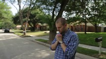 Man praying on a street in a neighborhood of homes.