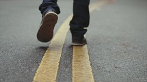 man walking on the yellow center lines of a road