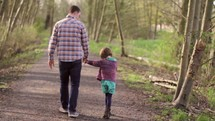 father walking holding hands with his daughter