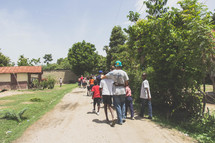 group of people walking on a dirt road in a village