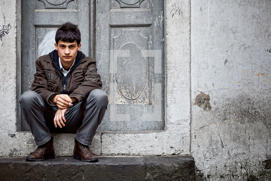 Turkish teen sitting on a door step