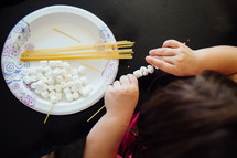 a child playing with spaghetti noodles and marshmallows to improve motor function