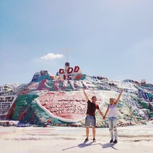 Couple holding hands with arms raised standing in front of a Salvation Mountain in Slab City, CA.