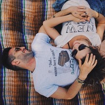 Smiling couple laying on a blanket outside.