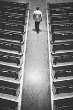 man walking down the aisle of an empty church