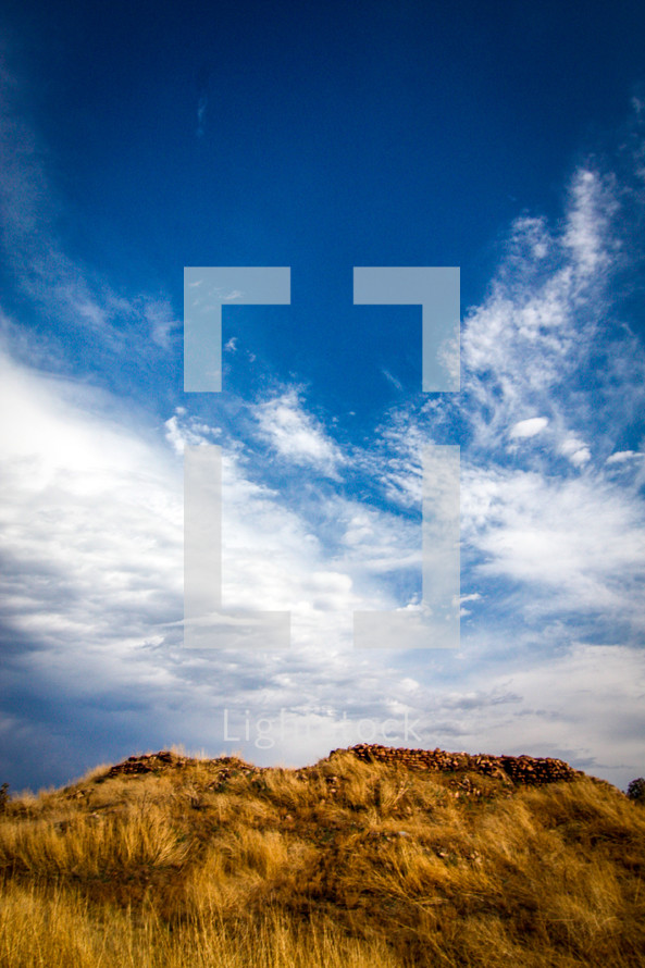 clouds and blue sky over a hill with tall grass