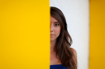 half of a woman's face peeking behind a yellow wall