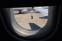 airplane at the gate with a member of the ground crew
