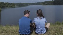 couple sitting on a shore by a lake
