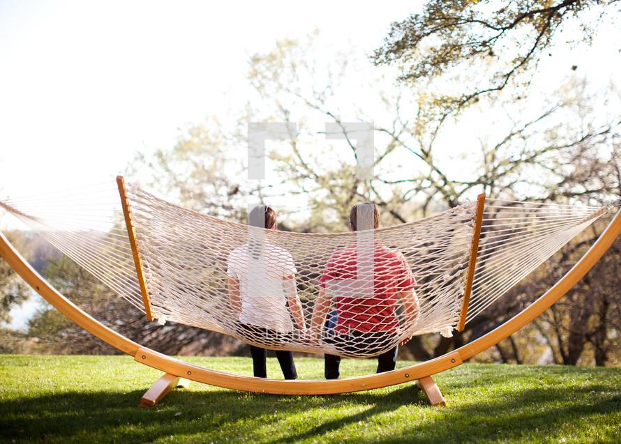 man and woman sitting on a hammock