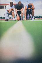 athletes kneeling in prayer on a football field
