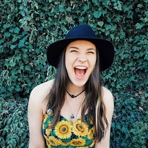 A laughing girl standing against a wall of ivy.