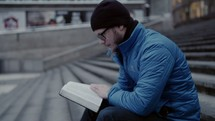 a man reading a Bible on steps in a city