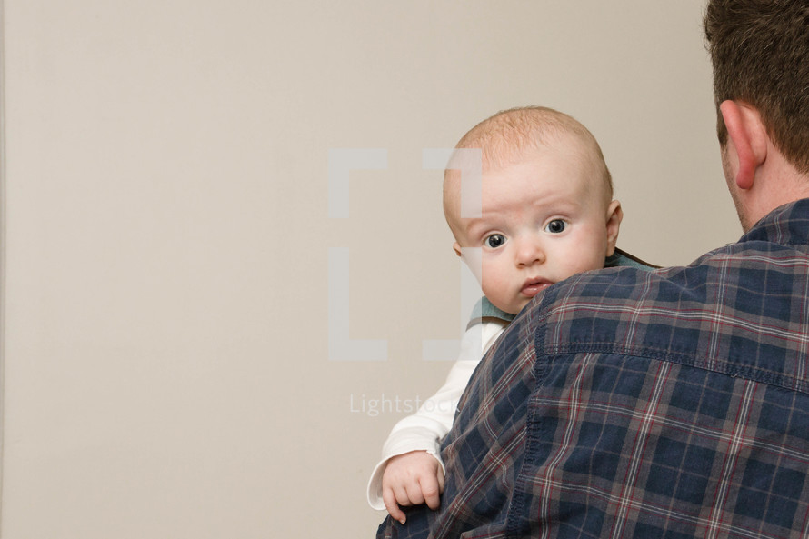 Father holding baby on shoulder