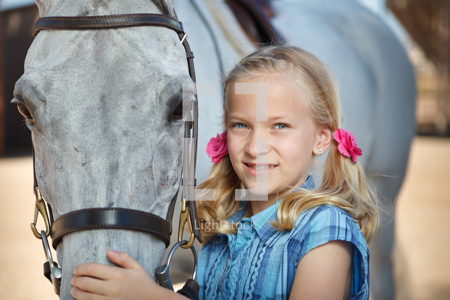 girl child in pig tails with a horse