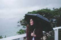 a woman standing under an umbrella