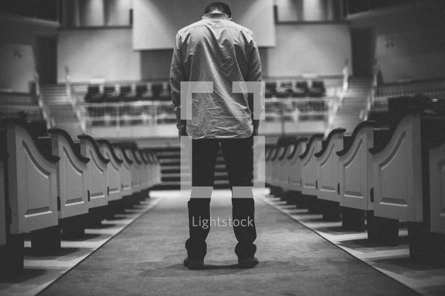 man looking down standing in the aisle of an empty church
