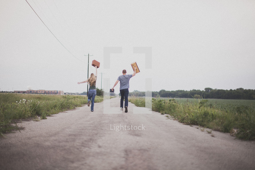 Couple running down the middle of a dirt road holding a Bible and suitcases.