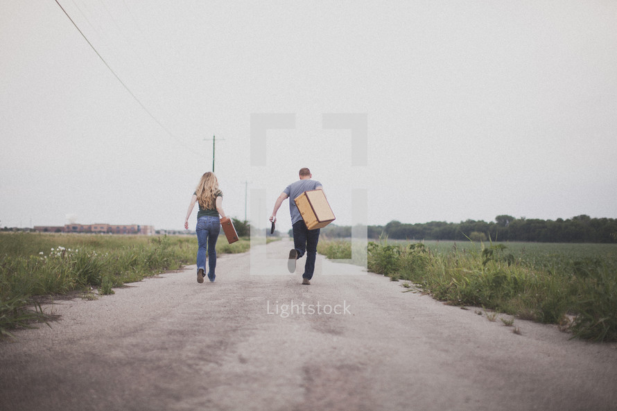 man and woman carrying luggage running down a road