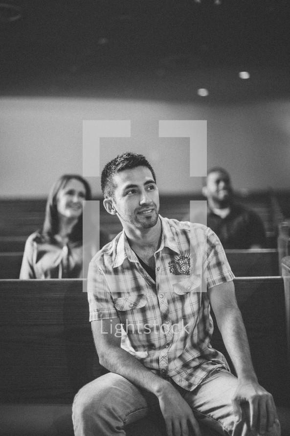 Smiling congregation sitting in pews.