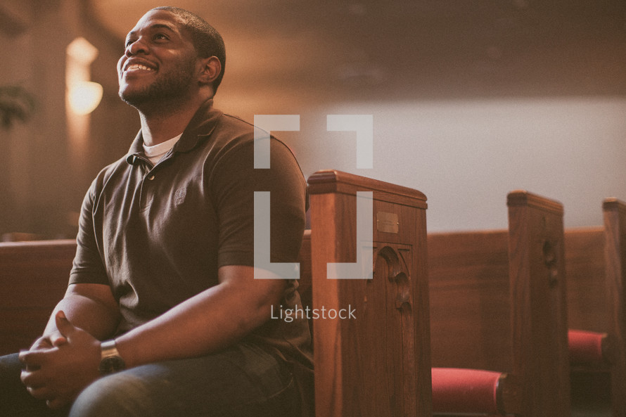 man sitting in a church looking up to God