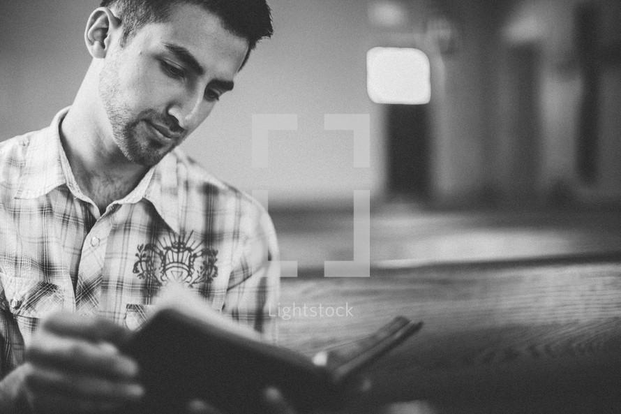 man reading a Bible in a church