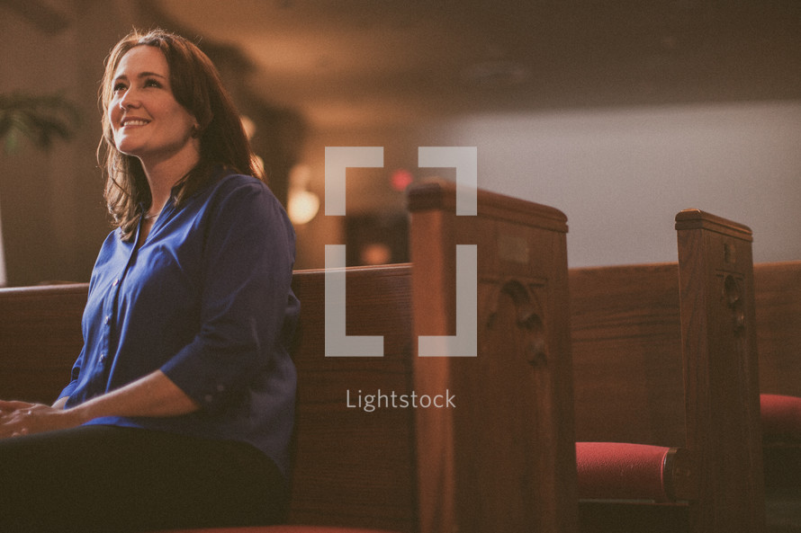 woman sitting in a pew in a church smiling