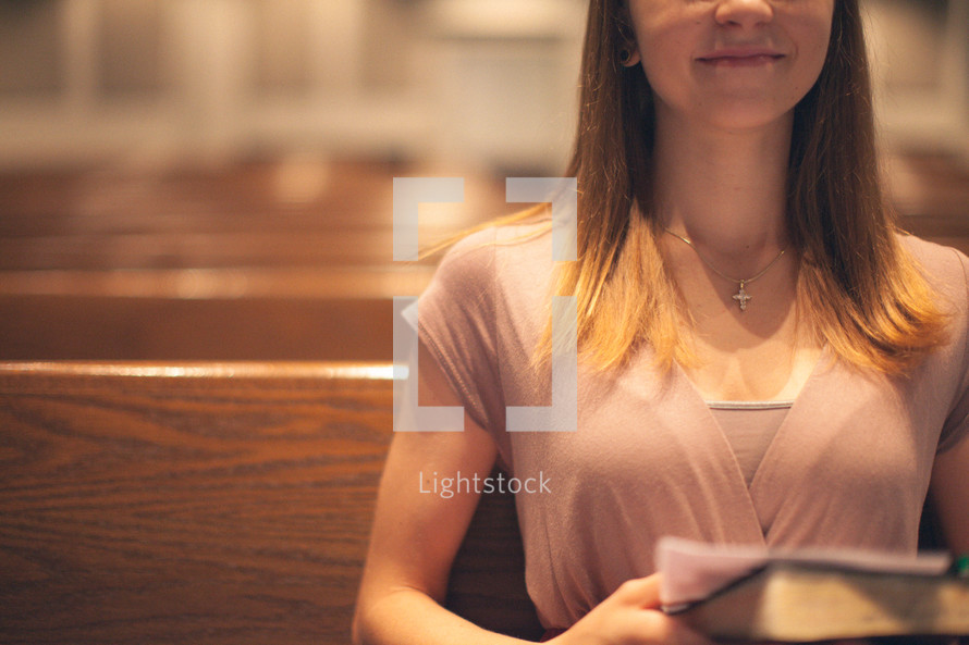 woman sitting in a church pew holding a Bible