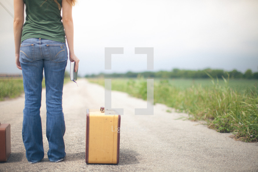 woman standing in the middle of a road next to suitcases