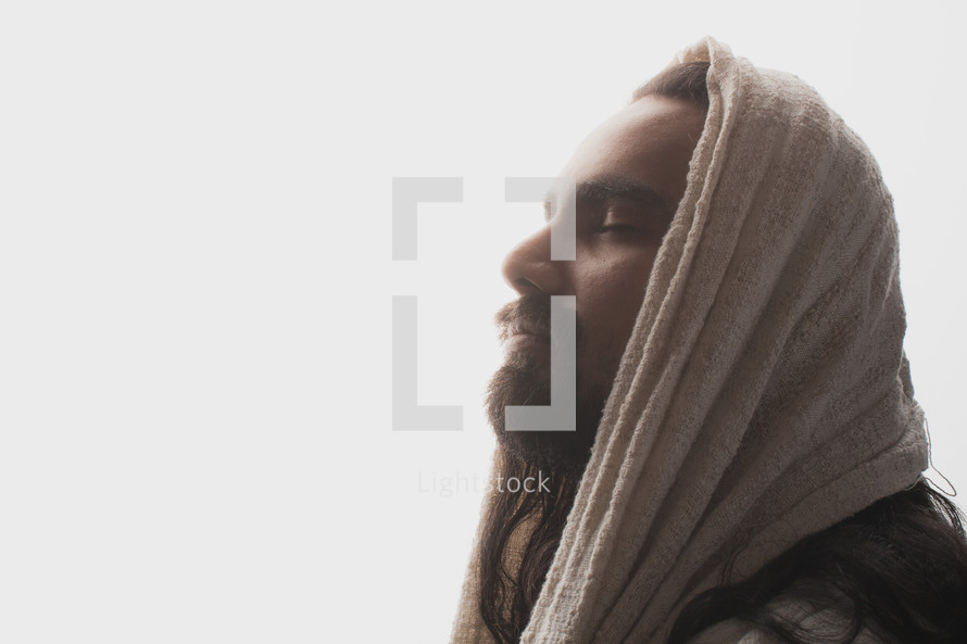 Hooded Jesus praying in the sunlight.