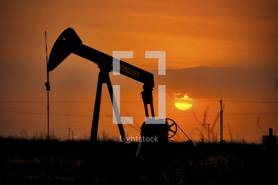 oil drill against an orange sunset
