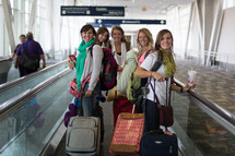 A group of young women walking through the airport with their suitcases