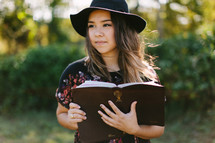 a teen girl in a hat reading a Bible