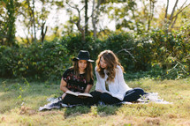 young women sitting on a blanket outdoors reading Bibles