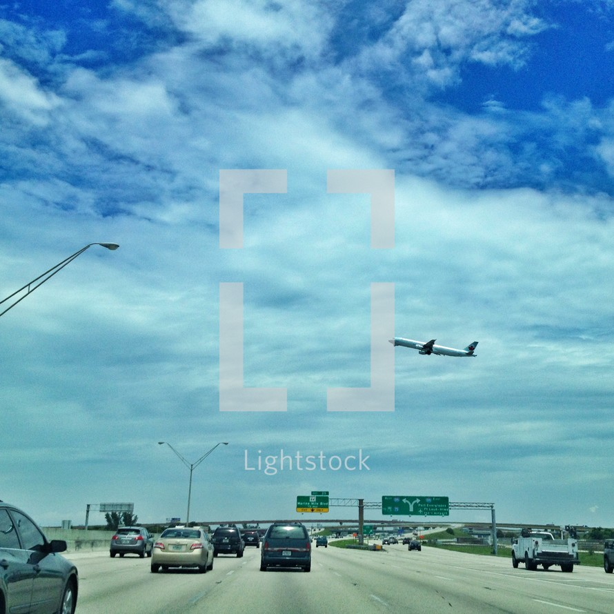 commercial airplane in flight over a highway