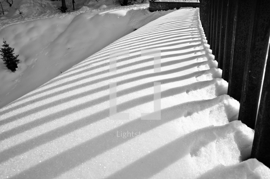 snow against fence rails