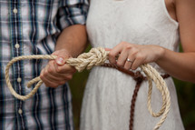 Couple tying a knot in a rope.