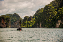 Boat sailing in the ocean water near tree covered mountains.