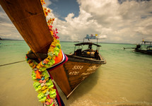 Fishing boat coming ashore in the ocean water in Thailand.