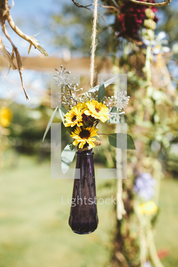 vase of flowers hanging from a tree for an outdoor wedding reception