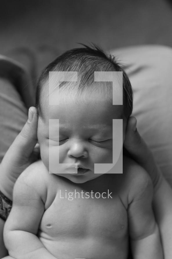 Father holding sleeping newborn baby boy