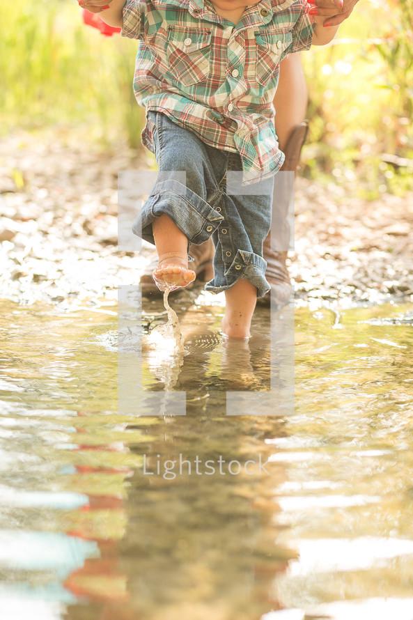 toddler walking and splashing in a pond
