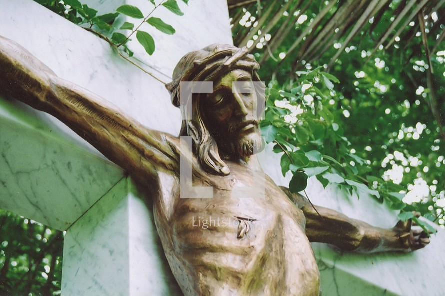 Jesus on the cross bronze statue of Jesus on a marble cross outdoor sculpture in a garden reminding people that Jesus went to the cross for the sins of all mankind.