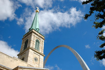Cathedral with a cross on the steeple near the Gateway Arch.