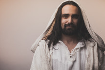 The resurrected Christ -- Smiling Jesus wearing a hooded cloak.