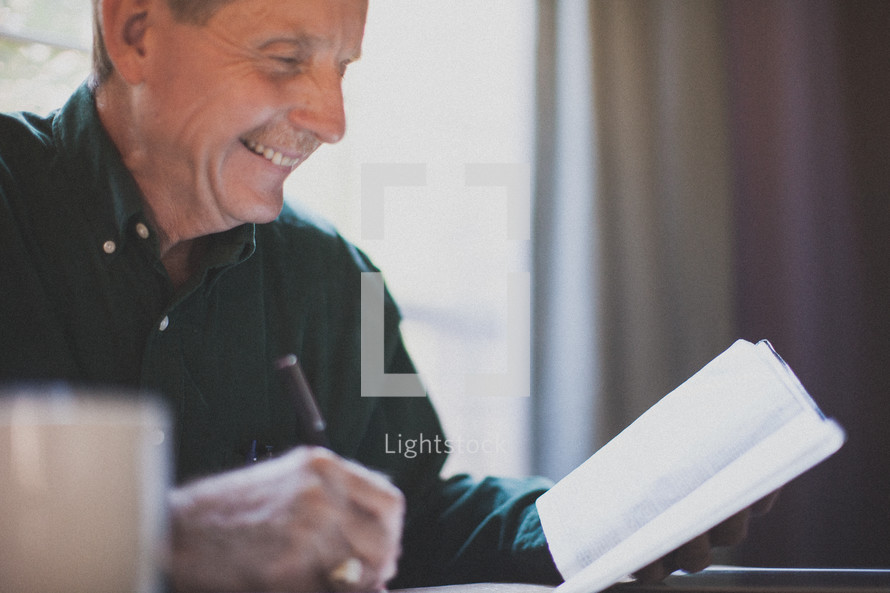 man reading a Bible and writing in a journal